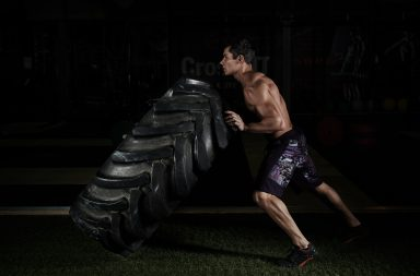 Crossfit training. Young sportsman with muscular body lifting heavy wheel in gym.